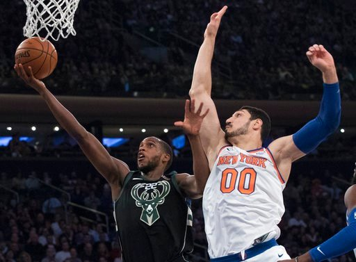 (AP Photo/Mary Altaffer). Milwaukee Bucks forward Khris Middleton (22) goes to the basket past New York Knicks center Enes Kanter (00) during the first half of an NBA basketball game, Tuesday, Feb. 6, 2018, at Madison Square Garden in New York.