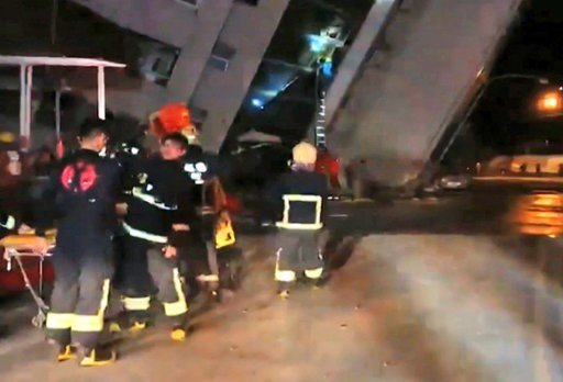 (EBC via AP). In this image from TV, emergency services attend after a building collapsed on its side, as a man climbs a ladder to gain access to the building, centre background, after an early morning earthquake in Hualien County, eastern Taiwan, earl...