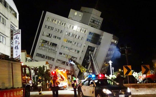 (AP Photo/Tian Jun-hsiung). Rescuers are seen entering a building that collapsed onto its side from an early morning 6.4 magnitude earthquake in Hualien County, eastern Taiwan, Wednesday, Feb. 7 2018.  Rescue workers are searching for any survivors tra...