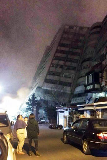 (Hualien County Fire Bureau via AP). In this photo released by Hualien County Fire Bureau, Taiwanese people watching a building that collapsed on its side from an early morning earthquake in Hualien County, eastern Taiwan, early Wednesday, Feb. 7 2018....