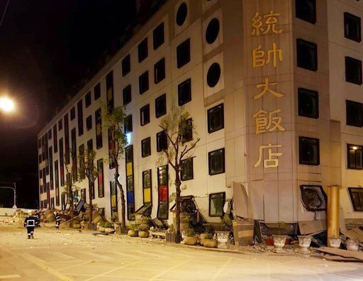(Hualien County Fire Bureau via AP). In this photo released by Hualien County Fire Bureau, debris around a building as rescue workers gain entry after the building collapsed onto its side following an early morning earthquake in Hualien County, eastern...