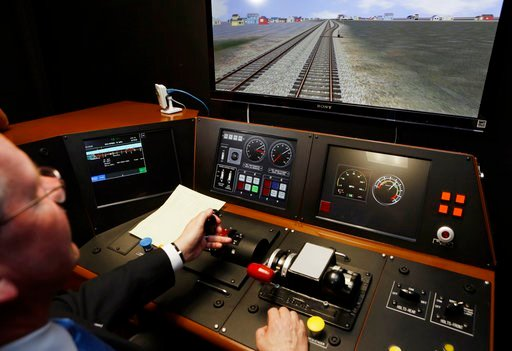 (AP Photo/Damian Dovarganes, File). FILE - In a Feb. 20, 2014 file photo, Metrolink Director of Operations, R.T. McCarthy, demonstrates Metrolink's implementation of Positive Train Control, (PTC) at the Metrolink Locomotive and Cab Car Simulators train...