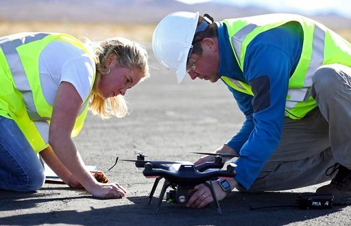 (AP Photo/Isaac Brekken). Jessica Balik, left, and Keven Gambold, right, CEO of Unmanned Experts, prepare a drone for a demonstration at the Searchlight airport in Searchlight, Nev., on Wednesday, Jan. 17, 2018. Gambold, a hacking target, said his own ...