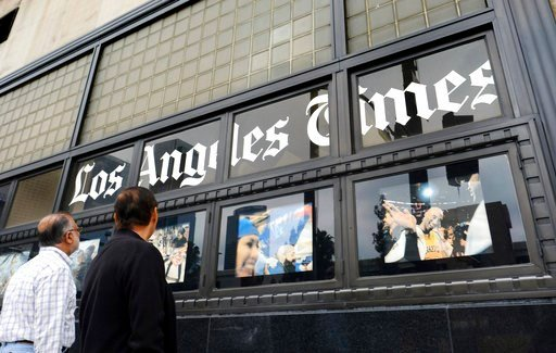 (AP Photo/Richard Vogel, File). FILE - In this May 16, 2016, file photo, pedestrians look at news photos posted outside the Los Angeles Times building in downtown Los Angeles. The Los Angeles Times is reporting its parent company is in talks to be sold...