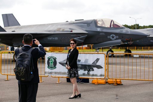 (AP Photo/Yong Teck Lim). Visitors take a photo with an F-35B fighter jet parked at the static display area during the Singapore Airshow Wednesday, Feb. 7, 2018, in Singapore.