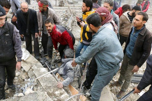 (Syrian Civil Defense White Helmets via AP). This photo provided by the Syrian Civil Defense group known as the White Helmets, shows men pulling a survivor from the rubble after airstrikes hit a rebel-held suburb near Damascus, Syria, Monday, Feb. 5, 2...