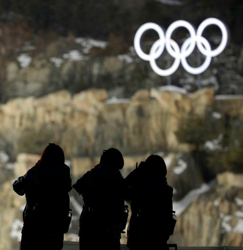 (AP Photo/Charlie Riedel). Volunteers wait for the start of practice for the men's ski jumping competition in the 2018 Winter Olympics at the Alpensia Ski Jumping Center in Pyeongchang, South Korea, Wednesday, Feb. 7, 2018.