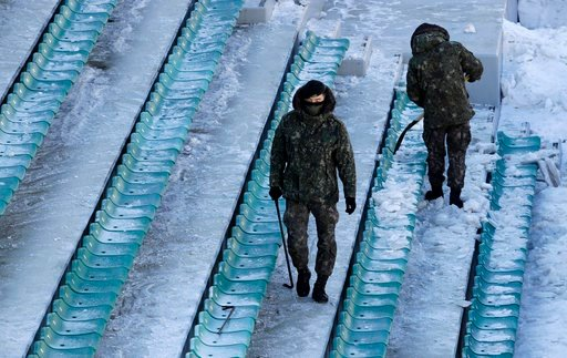 (AP Photo/Charlie Riedel). Soldiers clear snow and ice from the seating area at the Alpensia Ski Jumping Center ahead of the 2018 Winter Olympics in Pyeongchang, South Korea, Wednesday, Feb. 7, 2018.