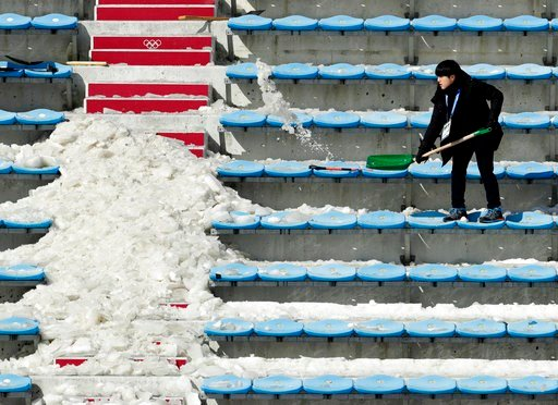 (AP Photo/Charlie Riedel). A workers shovels snow and ice from the seating area at the Alpensia Ski Jumping Center ahead of the 2018 Winter Olympics in Pyeongchang, South Korea, Wednesday, Feb. 7, 2018.