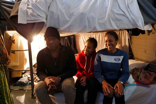 (AP Photo/Darko Vojinovic). A Cuban migrant Michael Amor, left, with his wife Ingrid, right, and daughter Samira sitting in their room in the center for refugees in Sot, about 100 km west from Belgrade, Serbia, Thursday, Feb. 1, 2018.  Far away from sa...