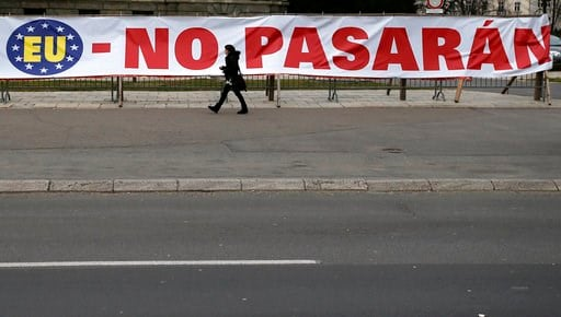 (AP Photo/Darko Vojinovic). A woman walks pass a part of a banner outside the Serbian parliament building praises Spanish refusal to recognise the former Serbian province of Kosovo which declared independence a decade ago in Belgrade, Serbia, Wednesday...