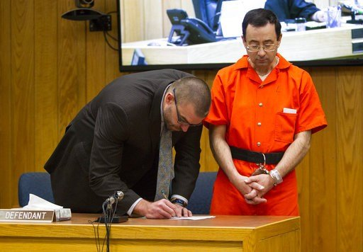 (Cory Morse /The Grand Rapids Press via AP). FILE- In this Feb. 5, 2018 file photo, Defense attorney Matthew Newberg, left, signs court documents after Judge Janice Cunningham sentenced Larry Nassar, right, at Eaton County Circuit Court in Charlotte, M...