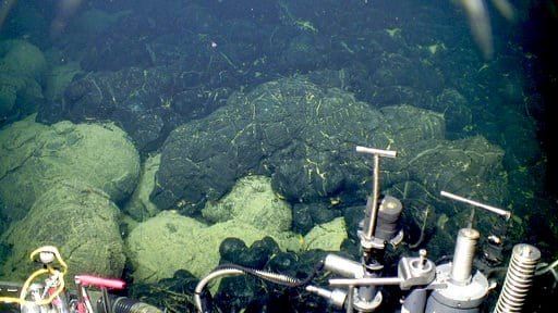 (Bill Chadwick/Oregon State University, ROV Jason, Woods Hole Oceanographic Institution via AP). This 2015 image provided by the Woods Hole Oceanographic Institution shows the edge of the 2015 lava flow, above, at the Axial Seamount where it overlies o...