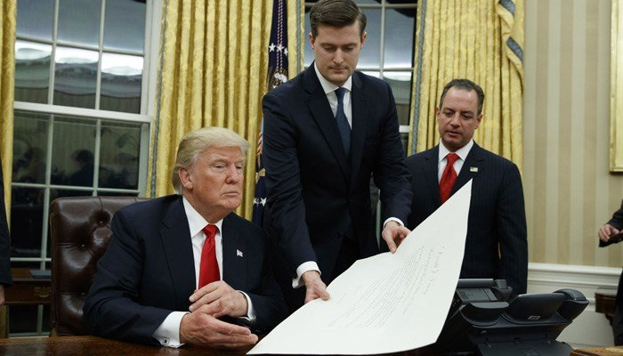 White House Chief of Staff Reince Priebus, right, watches as White House Staff Secretary Rob Porter, center, hands President Donald Trump a confirmation order for James Mattis as defense secretary Jan. 20, 2017, in the Oval Office. (AP Photo/Evan Vucci)