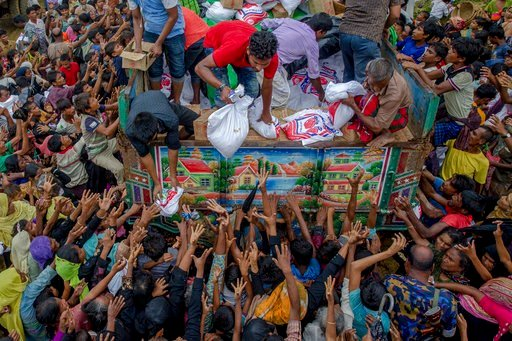 (AP Photo/Dar Yasin). FILE - In this Monday, Sept. 18, 2017, file photo, Rohingya Muslims, who crossed over from Myanmar into Bangladesh, reach out for food distributed by aid agencies near the Balukhali refugee camp in Cox's Bazar, Bangladesh. Massacr...