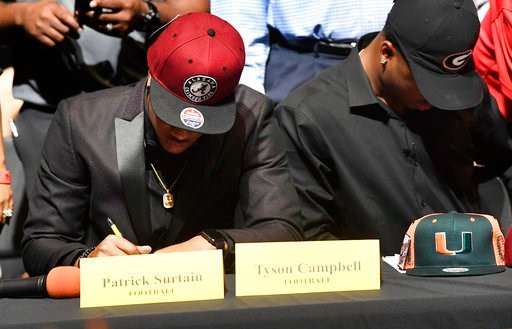 (Taimy Alvarez/South Florida Sun-Sentinel via AP). Patrick Surtain Jr., left, and Tyson Campbell, from the football team at American Heritage High School, sign to the University of Alabama and University of Georgia respectively, on national signing day...