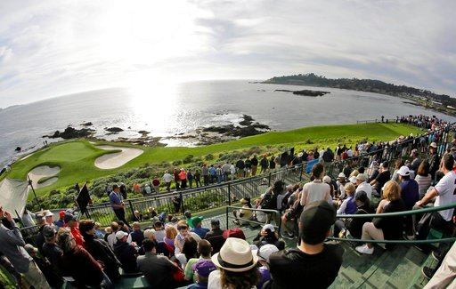 (AP Photo/Eric Risberg, File). FILE - In this Feb. 10, 2016, file photo taken with a fisheye lens, fans line the seventh hole of the Pebble Beach Golf Links to watch the inaugural $1 million celebrity hole-in-one event of the AT&T Pebble Beach Nati...