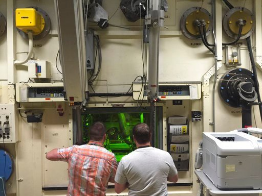 (AP Photo/Keith Ridler, File). FILE - In this May 11, 2015, file photo, Colt Killian, left, and Rob Cox manipulate radioactive material remotely behind a protective barrier at the Hot Fuel Examination Facility at the Idaho National Laboratory near Idah...