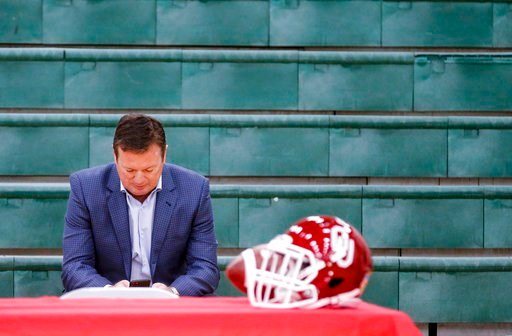 (Chris Landsberger/The Oklahoman via AP). Former University of Oklahoma football coach Bob Stoops uses his cell phone as he waits for his sons, Isaac and Drake Stoops, to announce they will be preferred walk-on for Oklahoma during national signing day ...