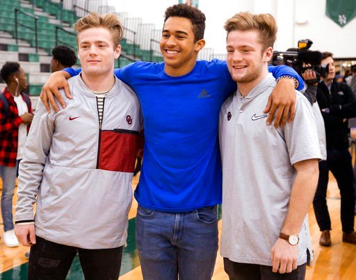 (Chris Landsberger/The Oklahoman via AP). CORRECTS TO FORMER OKLAHOMA HEAD COACH BOB STOOPS - Norman North's Ryan Peoples, center, poses for a photo with Drake, left, and Issac Stoops, after signing his letter of intent to play football for Northeaster...