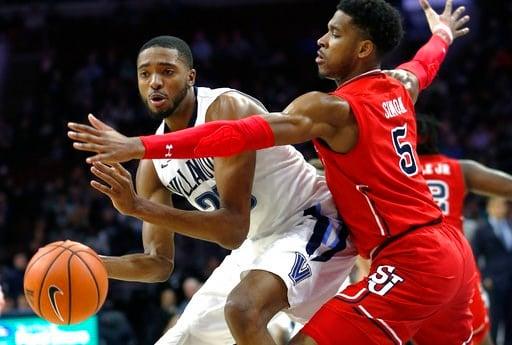(AP Photo/Laurence Kesterson). Villanova guard Mikal Bridges (25) moves around St. John's guard Justin Simon (5) during the first half of an NCAA college basketball game Wednesday, Feb. 7, 2018, in Philadelphia.