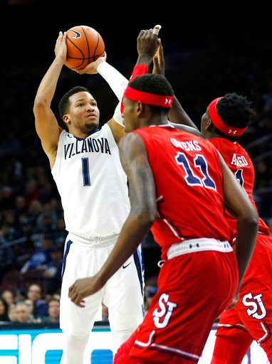 (AP Photo/Laurence Kesterson). Villanova guard Jalen Brunson (1) shoots over St. John's forward Tariq Owens (11) and another defender during the first half of an NCAA college basketball game Wednesday, Feb. 7, 2018, in Philadelphia.