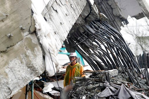 (AP Photo/Chiang Ying-ying). A rescuer checks damage during a search operation at a collapsed apartment building following a strong earthquake in Hualien County, eastern Taiwan, Thursday, Feb. 8, 2018. A magnitude 6.4 earthquake struck late Tuesday nig...