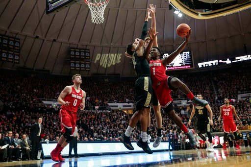 (AP Photo/AJ Mast). Ohio State forward Jae'Sean Tate, right, tries to shoot around Purdue defenders Vincent Edwards, left, and Matt Haarms during the first half of an NCAA college basketball game in West Lafayette, Ind., Wednesday, Feb. 7, 2018.
