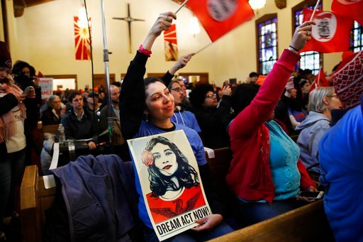 """(AP Photo/Jacquelyn Martin). Andrea Robertson, 25, with """"Make The Road Pennsylvania,"""" waves a flag during a rally in support of the Deferred Action for Childhood Arrivals (DACA) program Wednesday, Feb. 7, 2018, at the Lutheran Church of the Reformation..."""