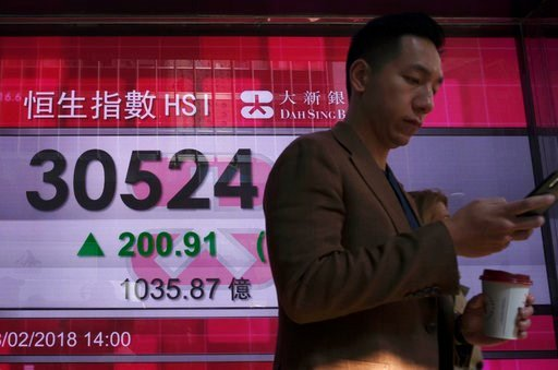 (AP Photo/Vincent Yu). A man walks past a bank electronic board showing the Hong Kong share index at Hong Kong Stock Exchange Thursday, Feb. 8, 2018. Asian stock markets were mixed Thursday with some benchmarks erasing early morning gains. Investors re...