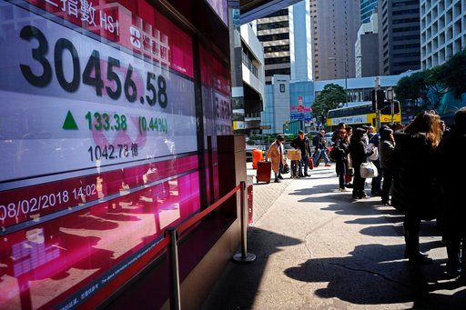 (AP Photo/Vincent Yu). People walk past a bank electronic board showing the Hong Kong share index at Hong Kong Stock Exchange Thursday, Feb. 8, 2018. Asian stock markets were mixed Thursday with some benchmarks erasing early morning gains. Investors re...