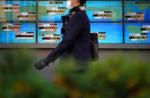 (AP Photo/Eugene Hoshiko, File). FILE- In this Jan. 10, 2018 file photo, a man walks past an electronic stock board showing Japan's Nikkei 225 index and other country's index at a securities firm in Tokyo. Asian stock markets were mixed Thursday, Feb. ...
