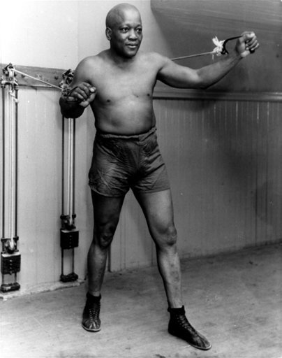 (AP Photo/File). FILE - In this 1932 file photo, boxer Jack Johnson, the first black world heavyweight champion, poses in New York City.  Black athletes have been finding a way to fight for social change for more than 100 years, from Jack Johnson, to M...