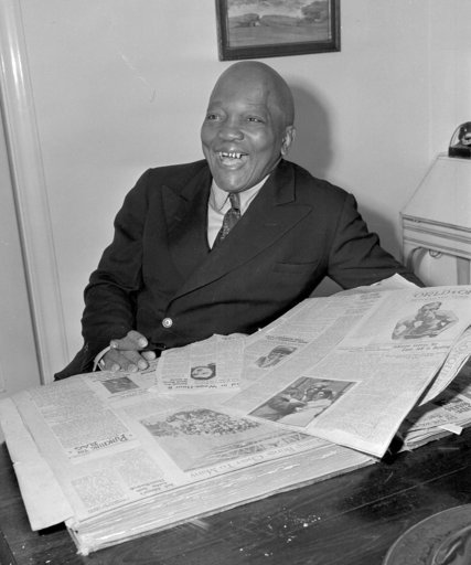(AP Photo/John T. Burns, File). FILE - In this Feb. 10, 1943, file photo, former boxer Jack Johnson sports some gold teeth while looking through a scrapbook of newspaper clippings in Los Angeles. There was no more potent or more closely guarded symbol ...
