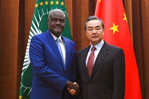 (Greg Baker /Pool Photo via AP). African Union Commission Chairperson Moussa Faki Mahamat, left, poses with Chinese Foreign Minister Wang Yi before a meeting in Beijing Thursday, Feb. 8, 2018.