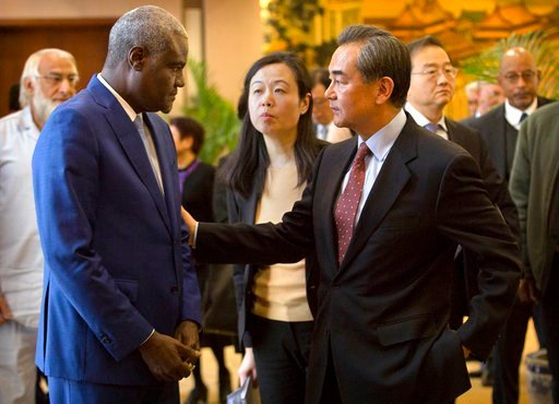 (AP Photo/Mark Schiefelbein). Chinese Foreign Minister Wang Yi, right, speaks with Chairman of the African Union Commission Moussa Faki Mahamat after a joint press conference at the Ministry of Foreign Affairs in Beijing, Thursday, Feb. 8, 2018. Chines...