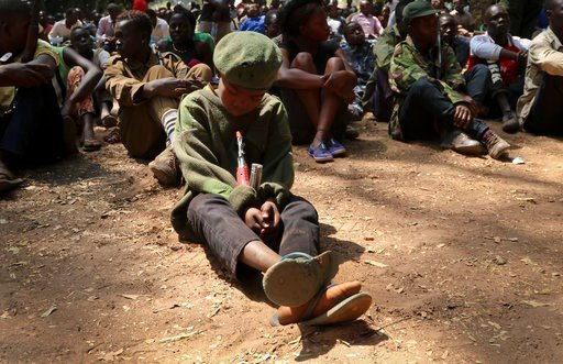 "(AP Photo/Sam Mednick). A young child soldier sits on the ground at a release ceremony, where he and others laid down their weapons and traded in their uniforms to return to ""normal life"", in Yambio, South Sudan Wednesday, Feb. 7, 2018. More than 300 c..."