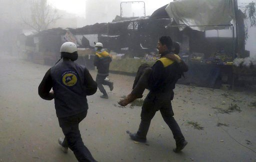 (Syrian Civil Defense White Helmets via AP). This photo provided by the Syrian Civil Defense group known as the White Helmets, shows a civil defense worker carrying a wounded man after airstrikes hit a rebel-held suburb near Damascus, Syria, Monday, Fe...