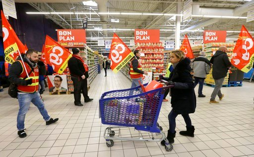 (AP Photo/Claude Paris). A woman pushes her trolley as employees of French retail giant Carrefour Group demonstrate against job cuts with union flags inside a Carrefour hypermarket, in Aix-en-Provence, southern France, Thursday Feb. 8, 2018. Carrefour ...