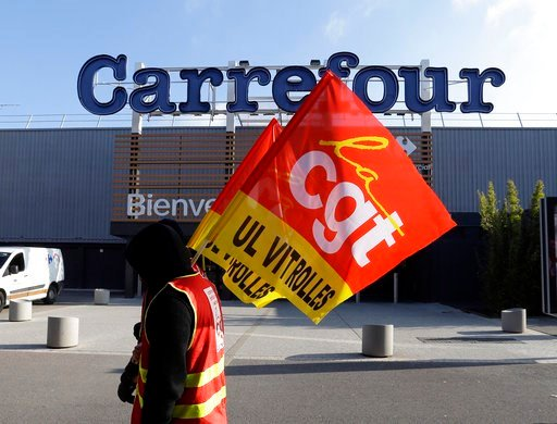 (AP Photo/Claude Paris). An employees of French retail giant Carrefour Group protests job cuts outside a Carrefour hypermarket, in Aix-en-Provence, southern France, Thursday Feb. 8, 2018. Carrefour CEO Alexandre Bompard announced last month cost saving...