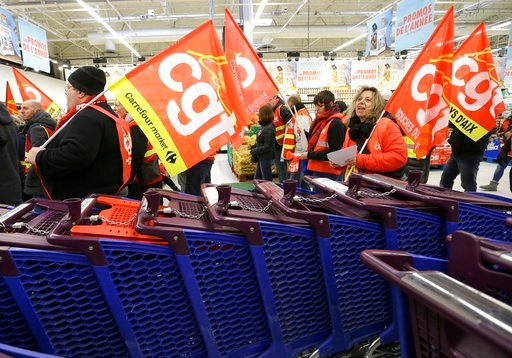 (AP Photo/Claude Paris). Employees of French retail giant Carrefour Group demonstrate with union flags inside a Carrefour hypermarket, in Aix-en-Provence, southern France, Thursday Feb. 8, 2018 to protest job cuts. Carrefour CEO Alexandre Bompard annou...