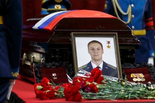 (Vadim Savitsky/Pool Photo via AP). Russian honorary guards stand next to a coffin with the body of Russian Roman Filipov, the pilot of the Su-25 jet who ejected after Syrian insurgents shot down his plane traded fire with militants on the ground and t...