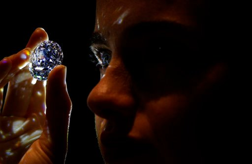"""(AP Photo/Alastair Grant). A 102.34, carat, D colour and flawless white diamond held by a model is displayed at Sotheby's auction house in London, Thursday, Feb. 8, 2018. The diamond is the world largest known round brilliant diamond to have achieved """"..."""