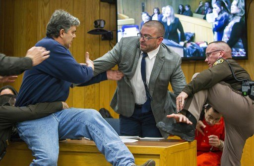 (Cory Morse/The Grand Rapids Press via AP). Randall Margraves, left, father of three victims of Larry Nassar, background right, lunges at Nassar in Eaton County Circuit Court in Charlotte, Mich., on Friday, Feb. 2, 2018. The incident came during the th...