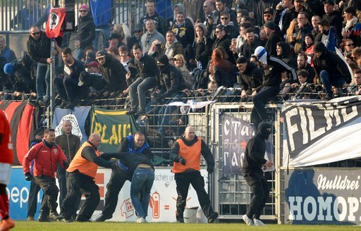 (Jan Kuppert/dpa via AP, file). FILE - In this April 28, 2017 file photo a Cottbus fan is being caught by security guards during a soccer match between SV Babelsberg and 03 - Energie Cottbus in Babelsberg eastern Germany. Despite being threatened with ...