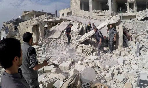 (Syrian Civil Defense White Helmets via AP). This photo provided by the Syrian Civil Defense White Helmets, which has been authenticated based on its contents and other AP reporting, shows civil defense workers and civilians inspecting a damaged buildi...