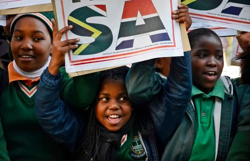 (AP Photo/Emoke Bebiak, File). FILE - In this July 19 2012, file photo, young children join hundreds of fans gathered at Johannesburg's O.R. Thambo Airport to bid farewell to the South Africa Olympic team members who were departing for the games in Lon...