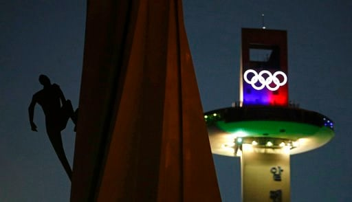 (AP Photo/Charlie Riedel, File). FILE - In this Feb. 4, 2018, file photo, a human figure appears to be climbing an Olympic Cauldron at the Pyeongchang Olympic Plaza as preparations continue for the 2018 Winter Olympics in Pyeongchang, South Korea. Afte...