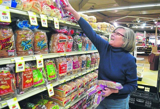(Jon Gard/The News-Dispatch via AP). Helen Sweeney, an independent distributor for Brownberry Premium Breads, stocks the shelves at Al's Supermarket ahead of another snowstorm, Thursday, Feb. 8, 2018, in La Porte, Ind.