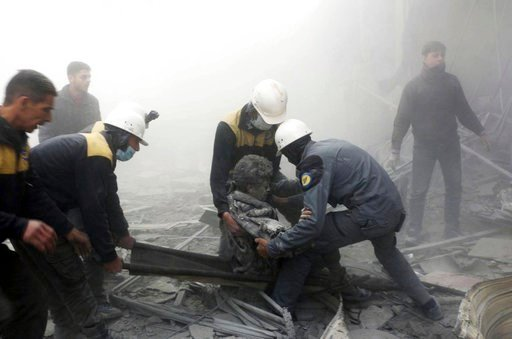 (Syrian Civil Defense White Helmets via AP). This photo provided by the Syrian Civil Defense White Helmets, which has been authenticated based on its contents and other AP reporting, shows civil defense workers carrying a wounded man after airstrikes h...